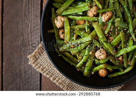 Green beans fried with chicken meatballs and garlic Asian style. top view - stock photo