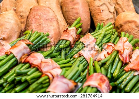 Green beans rolled in bacon and baked sweet potatoes - stock photo
