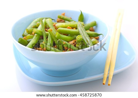 Green beans with minced meat and garlic in a blue bowl on a white background. Selective focu