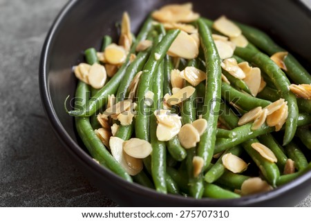 Green beans with toasted almonds, in black bowl over dark slate. - stock photo
