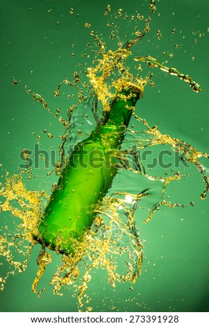 Green beer bottle with splashing liquid, freeze motion. - stock photo