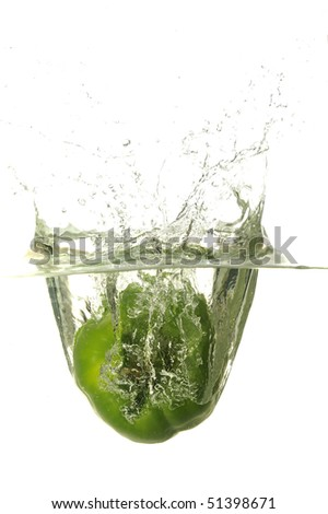 Green bell pepper splashing in water with bubbles in white background