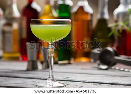 Green beverage in glass. Coupe glass with colorful liquid. Bartender's recipe of kiwi daiquiri. Sour lime juice.