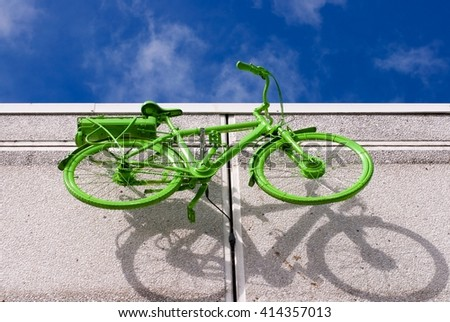 green bicycle on the grey wall