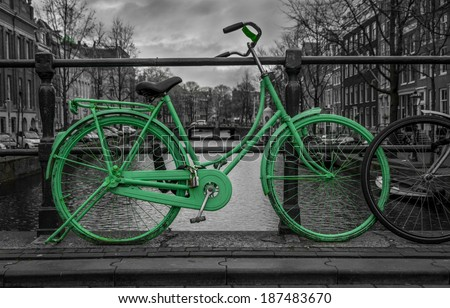 Green bike isolated on black and white over an Amsterdam canal. Very moody sky in background. - stock photo