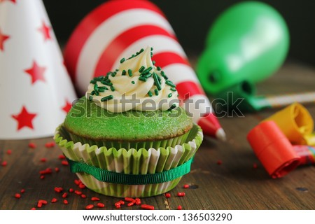 Green birthday cupcake with hats and blower in background