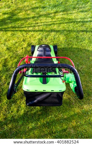 green black lawn mowers at garden with green grass - stock photo