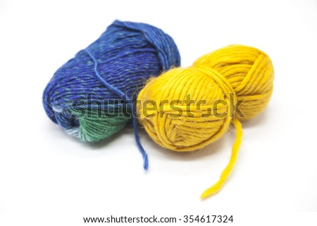 Green blue and  yellow ball of wool yarn for knitting close up on a white background. - stock photo