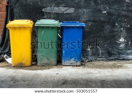 Green blue and yellow Trash can on concrete floor