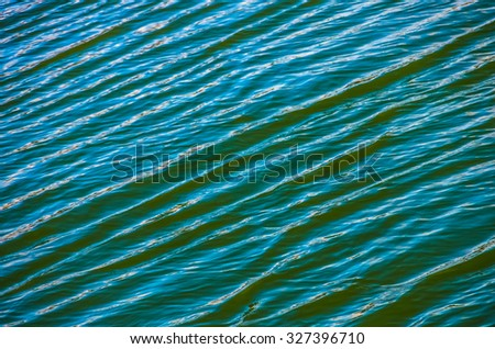 Green blue water texture with bright patch of light - stock photo