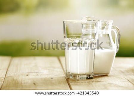 green blurred background and closeup of milk and wooden yellow space  - stock photo
