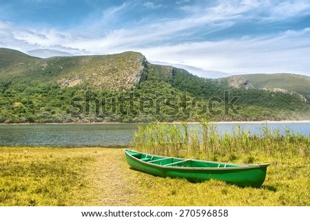 Green boat and lagoon. Shot in the Tsitsikamma National Park, Garden Route area, Western Cape, South Africa.  - stock photo