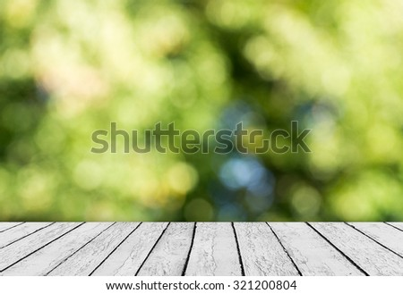 Green bokeh and sunlight and wood floor. Beauty natural background - stock photo