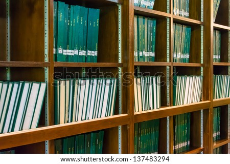Green books thesis for master degree on the bookshelf in university library, full of education knowledge - stock photo