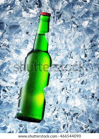 Green bottle of beer with drops on ice cubes