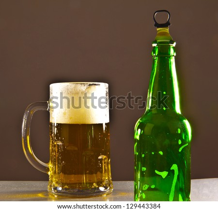 Green Bottle with Condensation and Glass of beer  on black background - stock photo