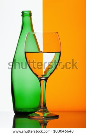 Green bottle with glass of water on a grey and orange background
