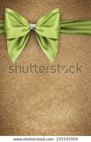 Green bow on texture of paper packaging - stock photo