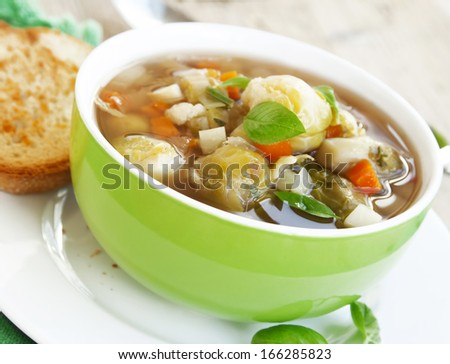 green bowl of fresh vegetable soup with basil leaves,healthy meal