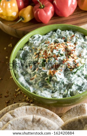 Green bowl of healthy vegetarian spinach artichoke dip with red crushed pepper and pita bread. - stock photo