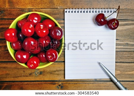 Green bowl with cherries fruit and notepad