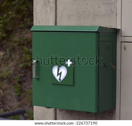 Green box with defibrillator (defibbrillateur) - stock photo