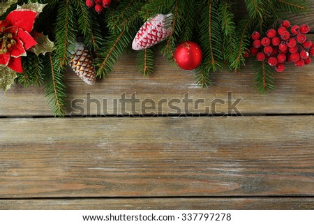 green branch and red xmas decorations on boards - stock photo