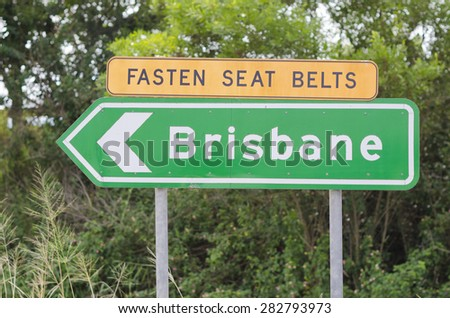 Green Brisbane sign with arrow on two posts. Above the green sign there is a yellow fasten seat belts sign. Background has out of focus bush.