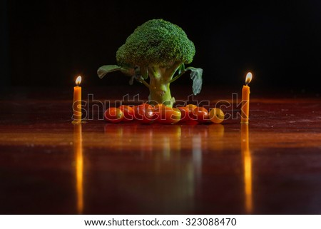 Green broccoli on a wooden table in low light conditions.