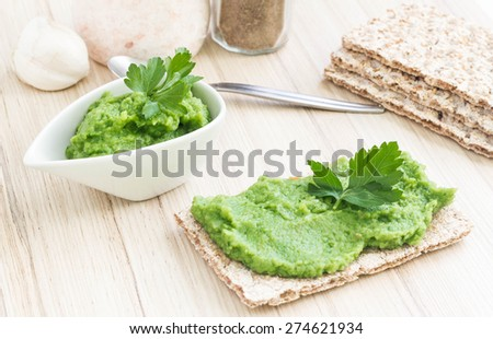 Green broccoli puree with rusk on a wooden table. - stock photo