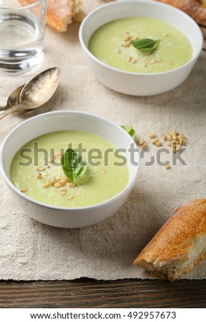 Green broccoli soup in white bowl, food closeup