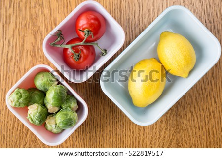 Green brussel sprouts, ripe yellow lemons, and ripe red tomatos in containers from above.