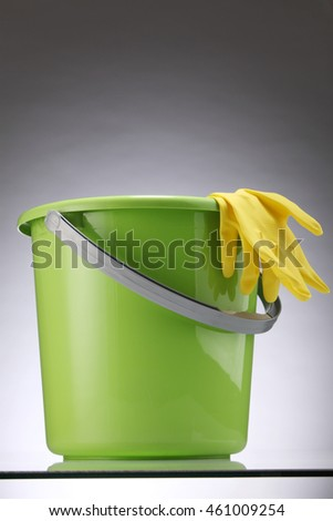 green bucket with yellow hand glove