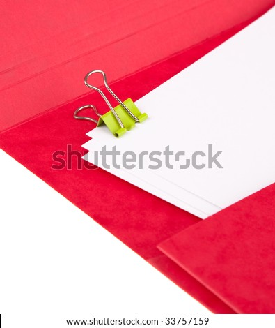 Green bulldog clip holding papers in a red folder.