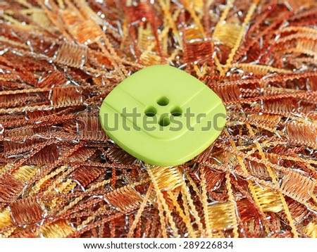 Green button on the brown thread background - stock photo