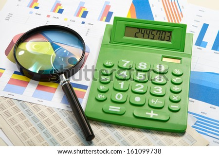 Green calculator and magnifier on a business background - stock photo