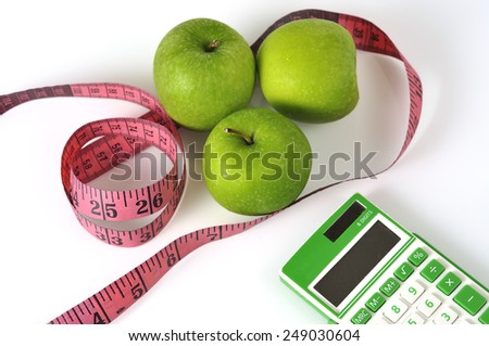Green calculator with Green Apple and Measure Tape on White Background, Healthy Lifestyle Concept and Selective Focus - stock photo