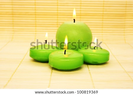 Green candles on bamboo background.
