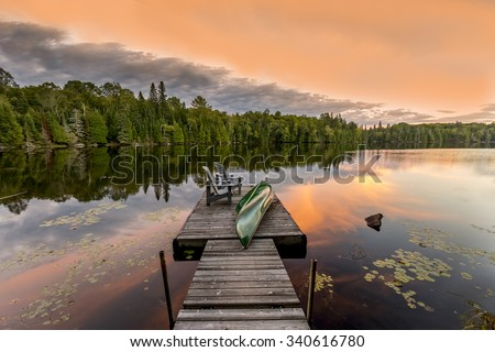 Green Canoe and Chairs on a Dock Next to a Lake at Sunset - Haliburton Highlands, Ontario, Canada - stock photo
