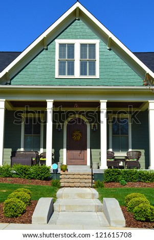 Green Cape Cod American Home with Large Front Porch - stock photo