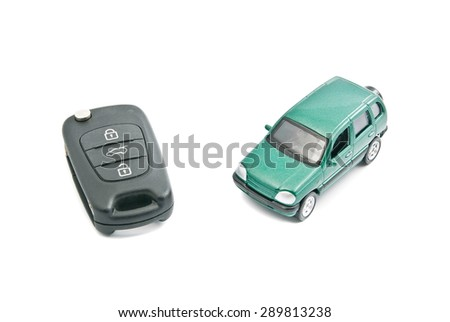 Green car and black car keys on white background