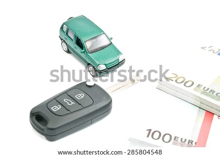 Green car, black car keys and euro banknotes on white - stock photo