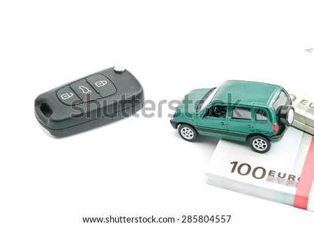 Green car, euro banknotes and black car keys on white