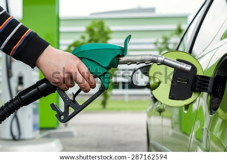 Green car on a gas station - stock photo