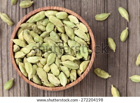 Green cardamom ayurveda plant aroma spice in a wooden bowl on vintage background - stock photo
