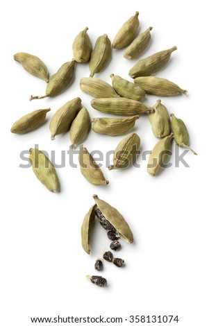 Green cardamom pods and seeds on white background - stock photo