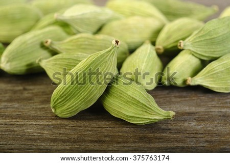 green cardamom pods on wooden background - stock photo