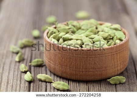 Green cardamom super food ayurveda asian aroma spice flavour in a wooden bowl on vintage background - stock photo