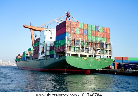 Green cargo ship in port, fully loaded with containers - stock photo