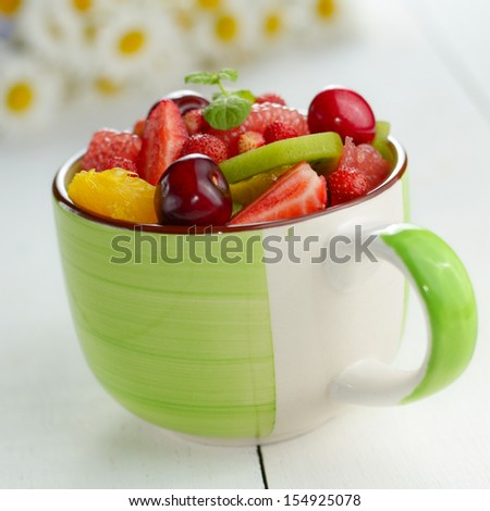 Green ceramic cup with mixed fruit salad on the white table